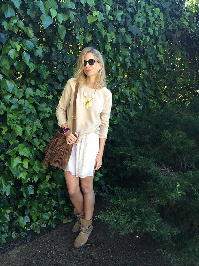 Look de María León con falda y sudadera de Des Petits Hauts, botas de Mango, gafas de sol Persol, collar de Mo by Maria Roca, bolso de flecos de The Code  y pulsera de Ibiza Passion.