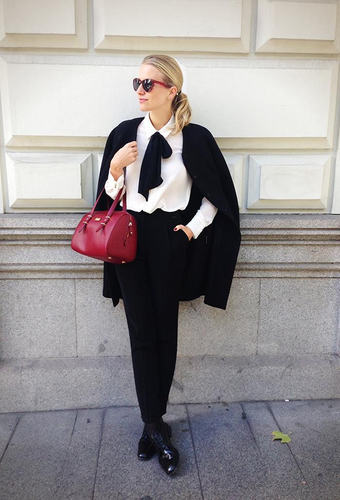 María León con pantalón negro, abrigo y bolso de Pedro del Hierro, blusa de Mango, zapatos de cordones de Zara y gafas de H&M.
