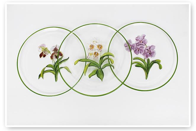 Platos de cristal francés pintados a mano con orquídeas, sobre unos de porcelana de falsa madera (diseño de Alberto Pinto)