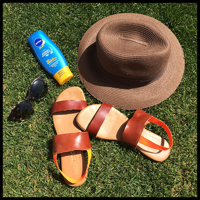 María León con look de moda para playa con sombrero de Papaya, sandalias de Neon Boots, crema solar de Nivea y gafas de Etnia Barcelona.