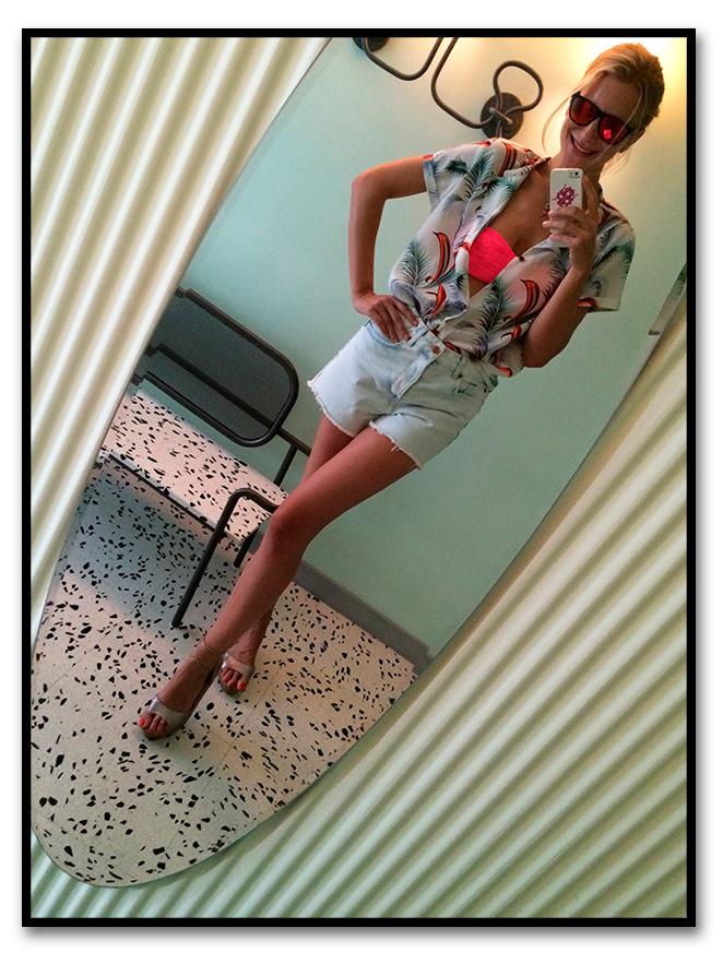 María León con look de shorts de TopShop, camisa de Scoth&Soda para Papaya, cuñas de esparto de Castañer, bolsa de flamencos de Pinkoco, suti bandeau fucsia de Pink y gafas de Life Italia