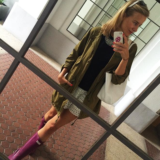 María León con look de verano con falda de Soy una chica normal que combiné con camiseta negra de Mango, collar de Pedro del Hierro, parka impermeable de Zara, botas Hunter, bolso de Pedro del Hierro y gafas Ray Ban.