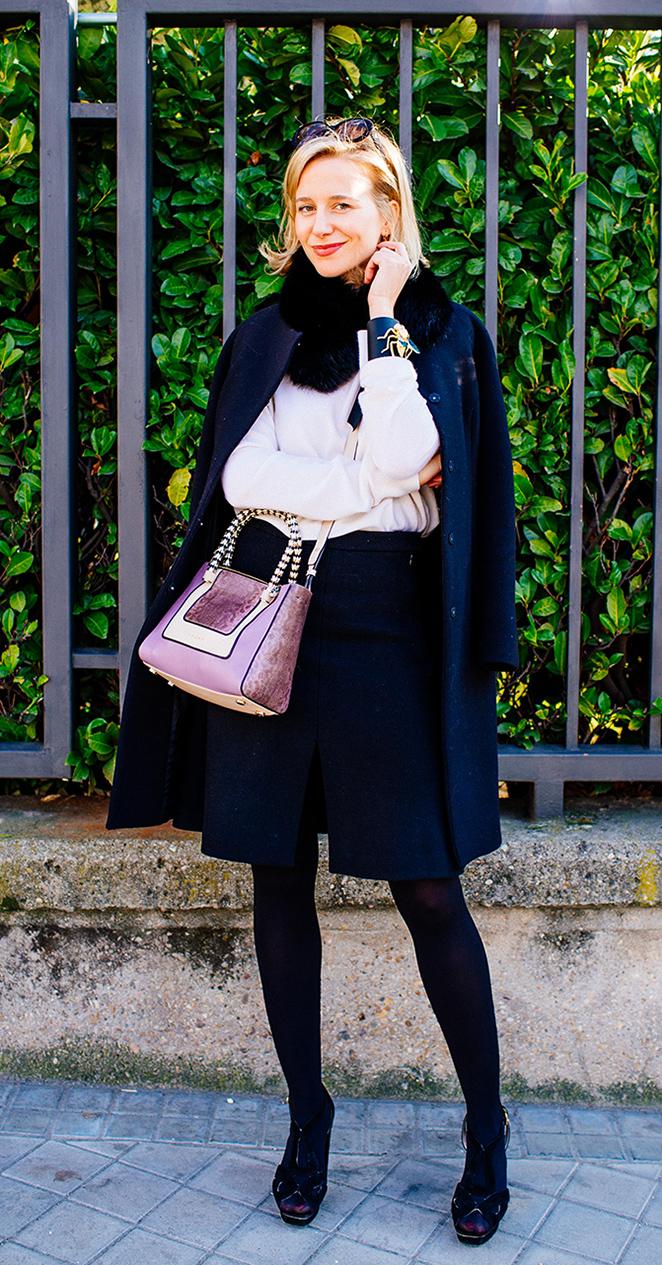 María León para Madrid Fashion Week con abrigo y cuello de pelo de Pedro del Hierro, falda y jersey de cashmere de Other Stories, brazalete de Jorge Vázquez, Gafas de Armani, sandalias de Prada, bolso de Bvlgari y como detalle beauty, manicura de Nails Couture.