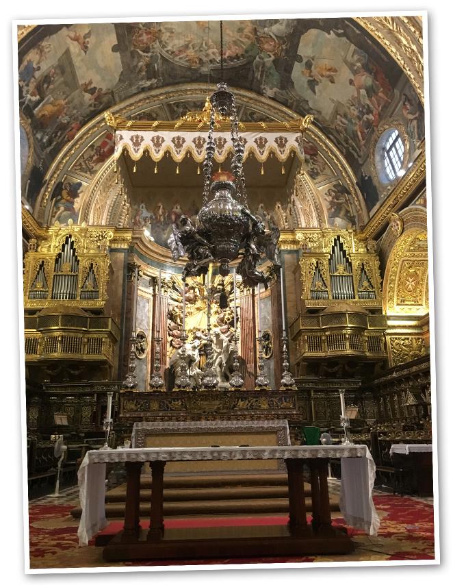 """Visita a la Concatedral de San Juan (1572). Es una espectacular Iglesia donde están representados, en distintas capillas, los caballeros de la orden de los diferentes reinados. Fue el Gran Maestre mallorquín, Nicolás Cotoner, el responsable de transformar la Iglesia del estilo sobrio que tenía en sus comienzos al barroco. El artista italiano Mattia Preti fue el responsable de ello. Además, dentro de la Concatedral se pueden admirar las obras más significativas de Caravaggio: """"Decapitación de San Juan Bautista"""" y """"San Jerónimo escribiendo"""". En Malta hay unos 583 templos entre iglesias, catedrales, concatedrales…"""